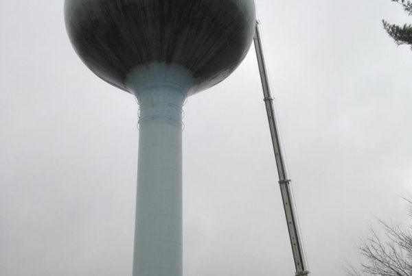 Using our crane with offset jib setting cell antennas on top of water tower.