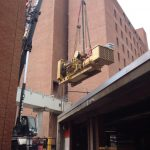 Hoisting one of the generatos out over the building.