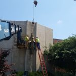 Working on taking the statue of the blessed mother off of the side of the building.