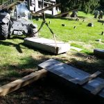 We are going to pick the gravestone flat and get it over near the base and then slowly stand it up by rendering the strap to the top and raising the forklift and letting the gravestone slide on its bottom to find center and then set it.