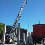 Using our 65 ton crane to set pre-cast concrete walkway and bleachers for a high school stadium.