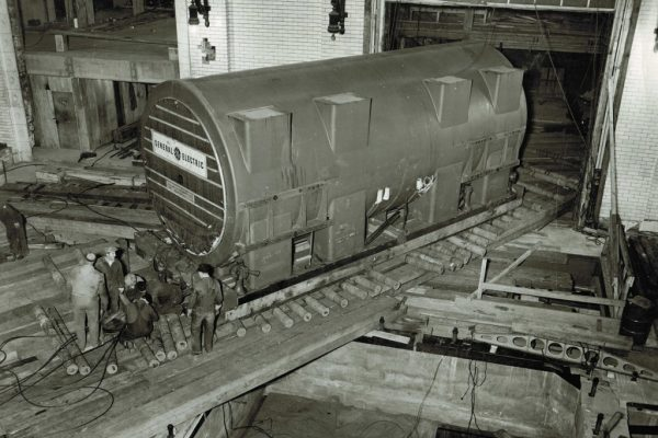 Mullins Rigging Fisk station-unit18-turbo generator-view showing stator being moved into building and set over foundation.